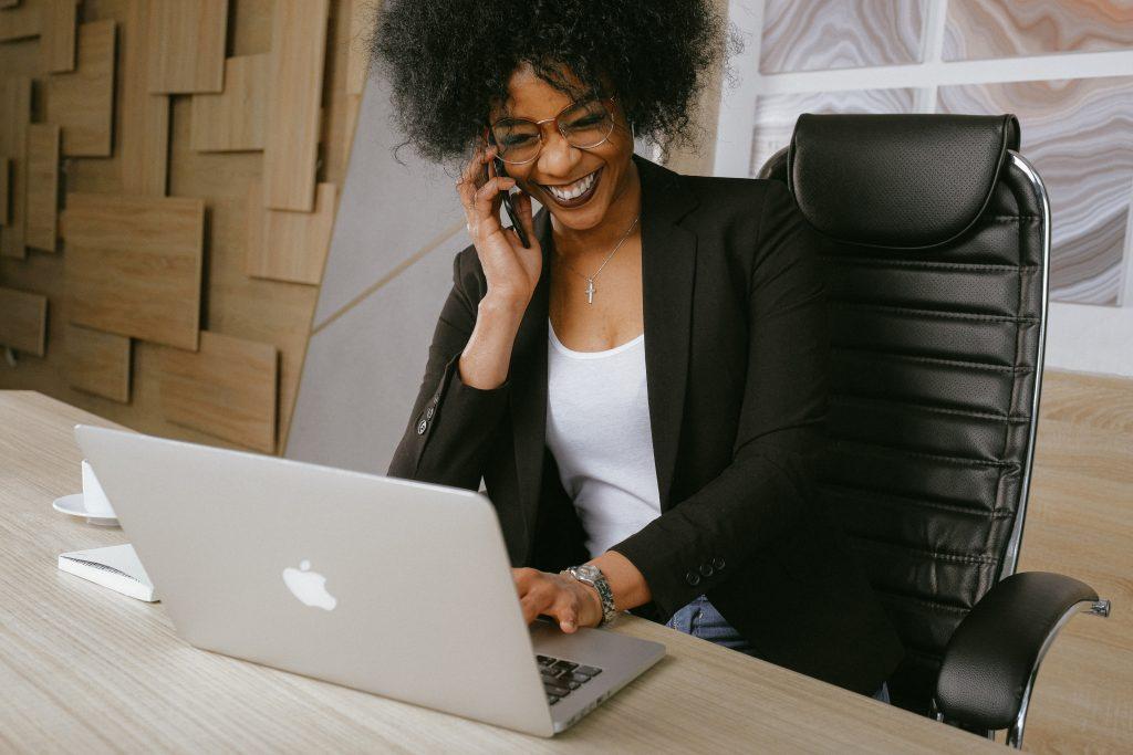 Femme assise sur une chaise de bureau ergonomique, travaillant sur un mac book