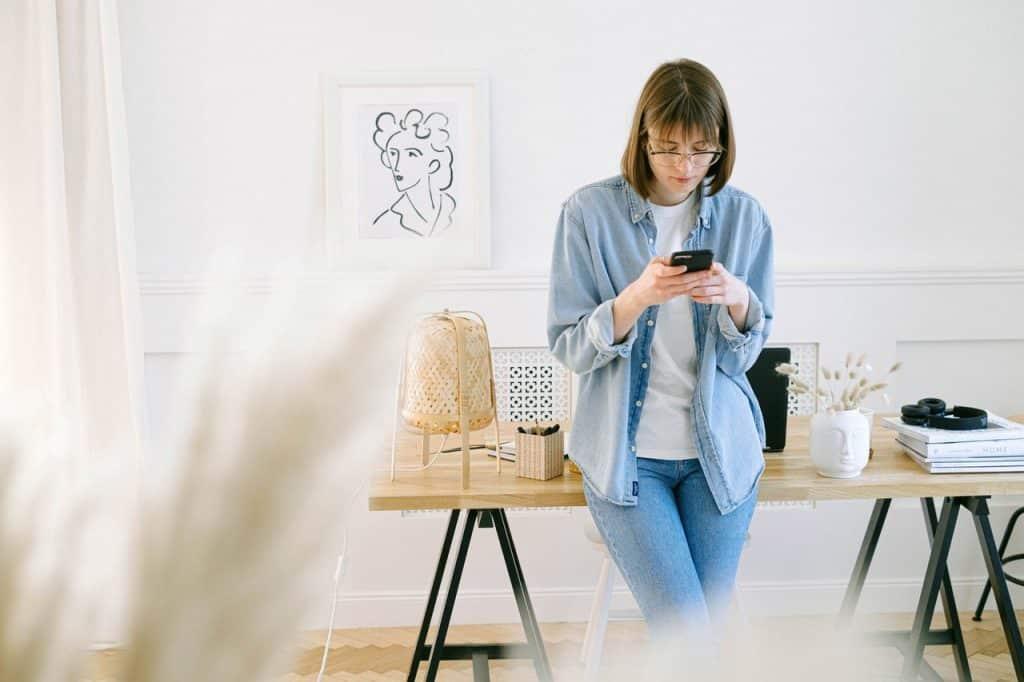Femme debout adossée sur un bureau en bois