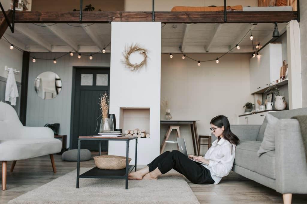 Femme assise dans salon naviguant sur son ordinateur